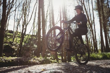 Mountain biker jumping while riding on dirt road in forest