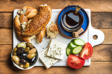 Turkish traditional breakfast with feta cheese, vegetables, olives, simit bagel and black tea on white ceramic board over wooden background. Top view
