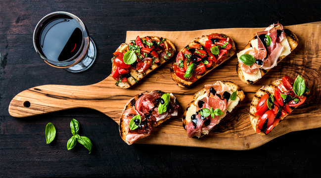 Brushetta set and glass of red wine. Small sandwiches with prosciutto, tomatoes, parmesan cheese, fresh basil, balsamic creme on rustic wooden board