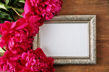 Beautiful peony and empty frame on wooden background