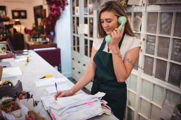 Female florist checking invoices while talking on telephone