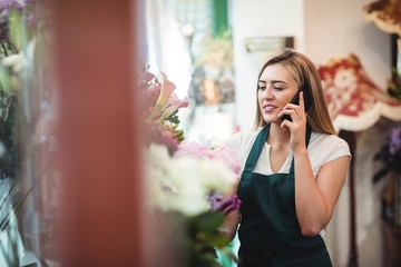 Female florist talking on mobile phone while arranging flowers