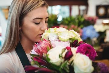 Female florist smelling flower bouquet