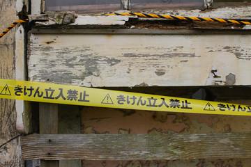 廃屋と立ち入り禁止の黄色いテープ