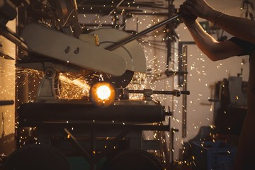 Blacksmith using saw machine in workshop