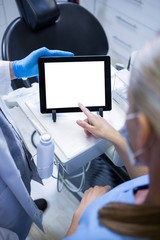 Dentist and dental assistant working on tablet