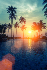 Tropical sunset and silhouettes of palm trees on sea beach.