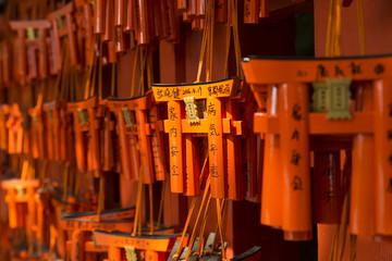 Ema (Holztafeln für Gebete und Wünsche) in Form von orange-farbenen torii (Torbogen) am Fushimi Inari Schrein in Kyoto, Japan.