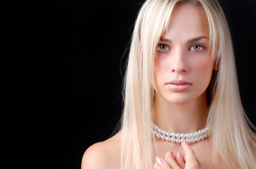 face of woman and pearl necklace