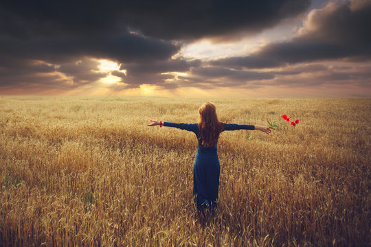 Back view of woman who stands toward the sunset in a wheat field with arms spread out, holding a poppy flower