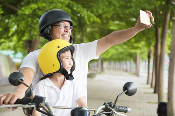 Father and daughter traveling and taking selfie on motorcycle