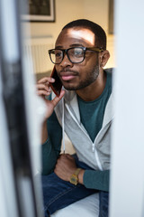 Handsome young black man using his mobile phone at home.