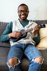 Handsome young black man playing the guitar at home.