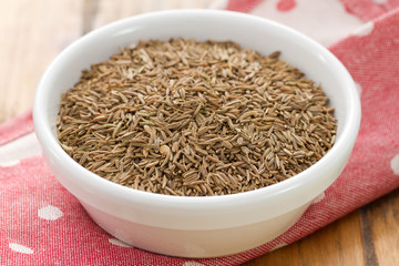 seeds of carum in white bowl on brown background