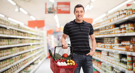 Cheerful guy shopping in a supermarket