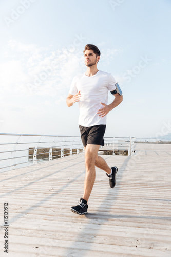 Man athlete running on wooden terrace for Terrace jogging track