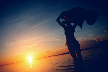 Wall Mural - Silhouette of young woman with shawl looking at sunset in the ocean
