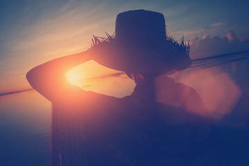 Fotomurais - Woman's silhouette in hat looking at sunrise at the ocean (lens flare effect and vintage color)