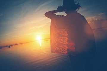 Fotomurais - Woman's silhouette in hat looking the sun rising over the horizon (lens flare effect and vintage color)