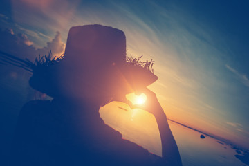 Fotomurais - Woman in straw hat making heart symbol with her hands at sunrise