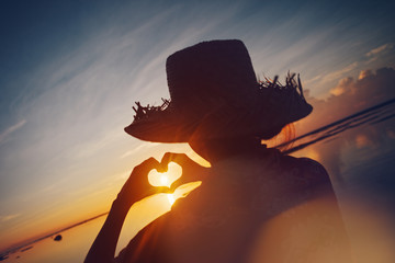 Fotomurais - Woman in straw hat making heart symbol with her hands at sunrise near the ocean (lens flare effect and bright color)