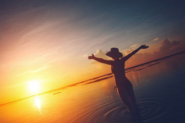 Fotomurais - Happy woman watching the sun rising over the horizon at the ocean