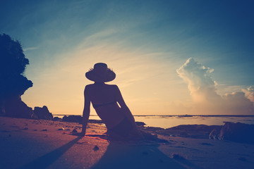 Fotomurais - Silhouette of woman in hat resting on the beach at sunrise (intentional vintage color)