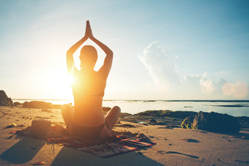 Fotomurais - Woman doing yoga on the beach at sunrise