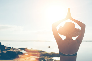 Fotomurais - Woman in straw hat doing yoga early in the morning on the beach (intentional sun glare and lens flare effect)