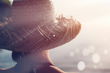 Fotomurais - Woman in straw hat standing near sparkling water (intentional sun glare and lens flare effect)