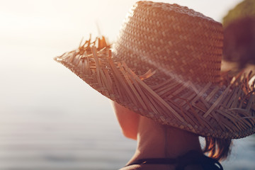 Fotomurais - Woman in straw hat standing near water and looking far away (intentional sun glare)