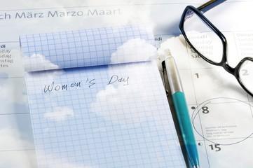 Desktop with calendar, notebook, pen and glasses. Blue cloudy sky textured.