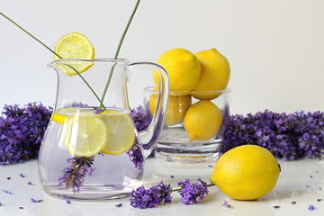 Fresh lavender lemonade drink served in glass jar with lemon slices. Summer fruit cold drink from water, lemons and lavender flowers. Still life with lavander lemonade in pitcher and whole lemons.
