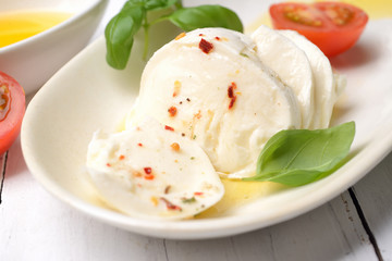 Delicious cheese mozzarella, tomato and basil leaves in white plate over white wooden background