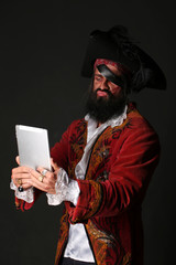 Portrait of man in a pirate costume with tablet