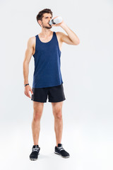 Full length portrait of a fitness man drinking water