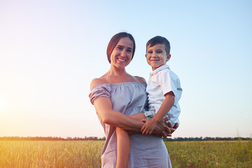 Beautiful woman and her small son on background of sunlit field