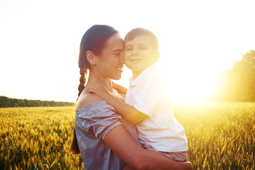 Beautiful woman holding small boy against sunset in the field