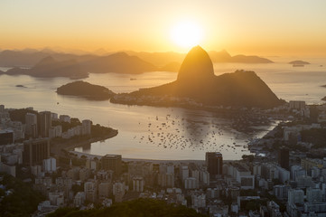 Scenic sunrise in Rio de Janeiro, Brazil glowing golden over Guanabara Bay with a skyline silhouette of Sugarloaf Mountain