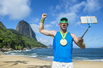 Gold medal athlete posing for a selfie with his mobile phone on a selfie stick at Red Beach in front of Sugarloaf Mountain, Rio de Janeiro, Brazil