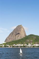 Single sailboat passes classic view of Pao de Acucar Sugarloaf Mountain standing above Botafogo Bay in Rio de Janeiro, Brazil