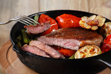 Beef steak with vegetables on a cast-iron frying pan close-up. Selective focus.