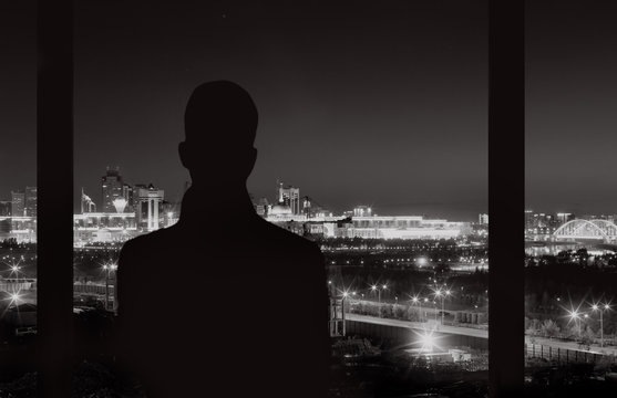 man looking to the window at night city
