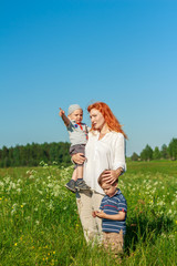 Beautiful red-haired mother playing with children in the field.