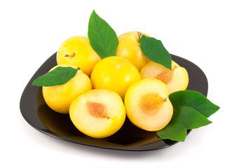 Yellow plums with leaves on a black plate isolated on white background