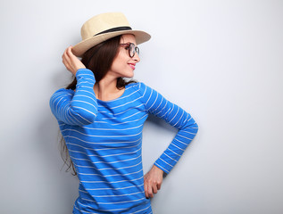 Happy woman posing in profile in glasses and straw hat on blue b