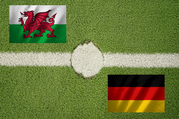 germany and wales flag on football green field and haft line