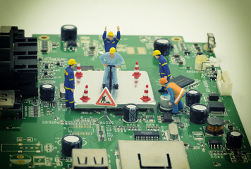 group of mini workers are try to repair a chip on mainboard