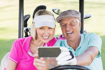 Mature couple taking selfie while sitting in golf buggy