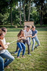 Young friends playing tug with rope in a park during the summer break from studies